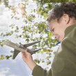 Boy standing outside with toy plane - Stockfoto