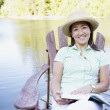 Portrait of woman sitting on deck by lake reading book — Stock Photo #23232808