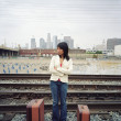 Young woman waiting beside train tracks - Stock Photo
