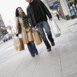Couple walking down sidewalk with shopping bags — Stock Photo