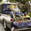 portrait of elderly man in lounge chair and sunglasses relaxing in back of pickup truck — Stock Photo