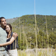 Couple with hiking stick hugging outdoors - Photo