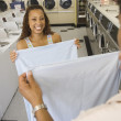 Couple folding sheets in laundromat - Stock Photo