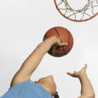 Low angle view of teenage girl shooting hoops — Stock Photo