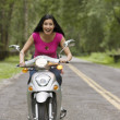 Portrait of woman riding scooter — Stockfoto