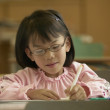 Young girl working in classroom — Stockfoto