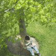 Overhead view of boy reading under tree — Zdjęcie stockowe