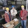 Three in warehouse looking at camera — Stockfoto