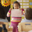 Young girl in classroom holding up her writing — Stock Photo