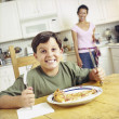 Excited boy preparing to eat pizza - Stock Photo