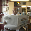 Senior man sitting in barber's chair with newspaper - Stock Photo
