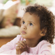 Young African American girl praying at bedside — Stock Photo #23233076