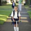 Portrait of girl in school uniform on scooter — Stock Photo