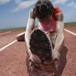 Female track runner stretching her legs - Stock Photo