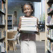 Stock Photo: Girl holding books in library