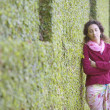 Stock Photo: Womleaning against hedge