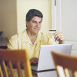 Man using credit card for online purchase - ストック写真