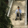 Business with laptop sitting on steps — Stock Photo