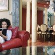 Woman reading book on couch — Stock Photo