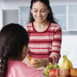 Mother peeling an orange for daughter — Stock Photo