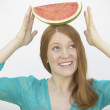 Woman balancing watermelon on her head - Stok fotoğraf