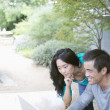 Asian couple using laptop outdoors — Stock Photo