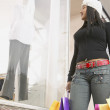 African American woman with bags window shopping — Stock Photo