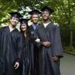 Four college graduates standing together — Stock Photo