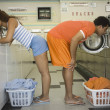 Stock Photo: Couple bent over washer and dryer in laundromat