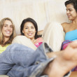 Three young women together on couch - Stock Photo