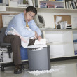 Overworked businessman shredding documents - Stok fotoğraf