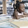Girl reading book in library — Stock fotografie