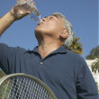 Senior Asian man with tennis racket drinking water — Stock Photo