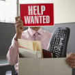Businessman holding up help wanted sign — Stock Photo