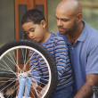 Father helping son fix bike — Stock Photo #23233868