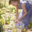 Stock Photo: Girl gathering Easter eggs