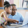 Father and daughter with laptop at restaurant - Stock Photo