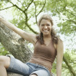 Looking up at a young woman in a tree — Stock Photo