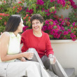Mother and daughter sitting on steps - Stock Photo