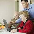 Man showing senior couple laptop — Stock Photo