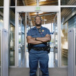 Security officer standing by entranceway - Stock Photo