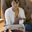 Woman reading newspaper in chair - Stock Photo