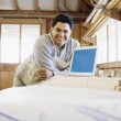 Portrait of man with laptop in workshop — Stock Photo