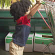 Young African American boy pushing shopping cart — Stock Photo #23234162