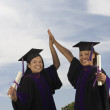 Female graduates giving high fives - Stock Photo