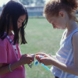 Two girls playing with electronic toys — ストック写真