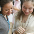 Two teenage girls with headsets listening to music — Stock Photo