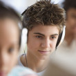 Teenagers in computer lab wearing headsets - ストック写真