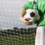 Lower section of girl holding soccer ball — Stock Photo