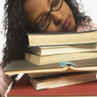 Young woman sleeping on a pile of books - Stock Photo